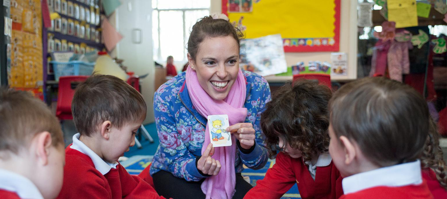 Teacher showing a card to a group of children